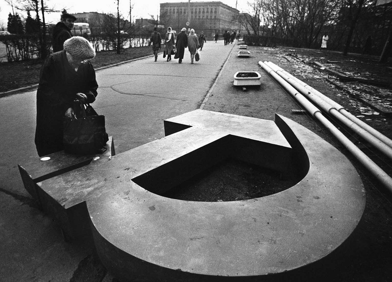 A woman reaches into her bag, which rests on a fallen Soviet hammer-and-sickle on a Moscow street in 1991.