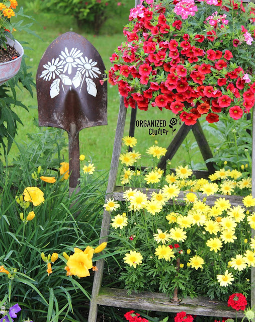 Photo of a shovel head stake stenciled with daisies.