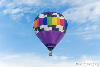 Cramer Imaging's fine art photograph of one purple rainbow hot air balloon taking flight in Panguitch Utah with a blue partly cloudy sky