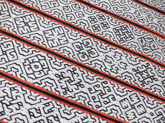 Tablet woven bands in black and white with orange edges, decorated with geometric motifs, arranged diagonally across the frame
