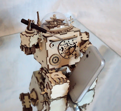 Wooden robot with a screw driver in one hand, holding an old cell phone up with a leg and the other hand, about to disassemble the phone.