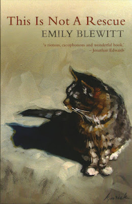 "The cover artwork is ""The Bitz"" by Karin Jurick and shows a tabby cat flecked with white sat on the ground, looking off to the left, over its own shadow. It appears to be painted in oils."