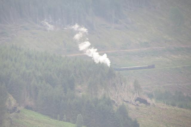 A long-distance shot of a steam train across the valleys.