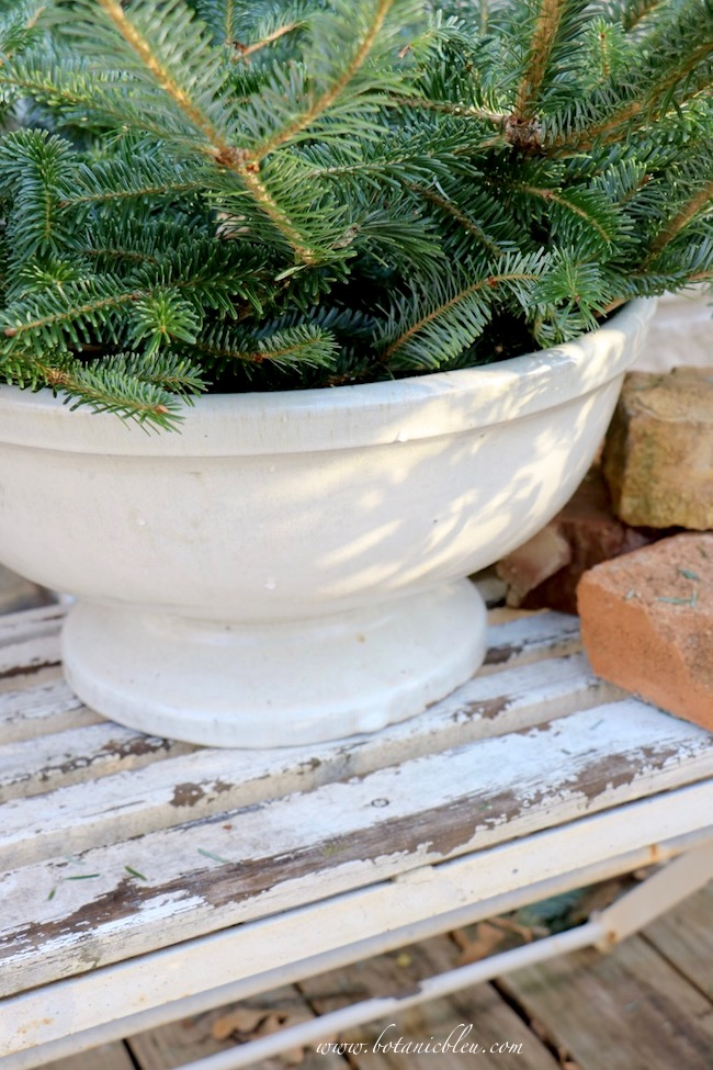 The rim of a large, deep ceramic flower pot helps stabilize the best ever greenery idea of fresh wreath