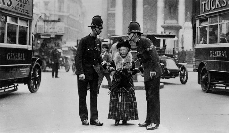 Vintage photo of two tall Bobbies lean over a very small, elderly woman standing in the middle of the street. Police Aesthetics. marchmatron.com