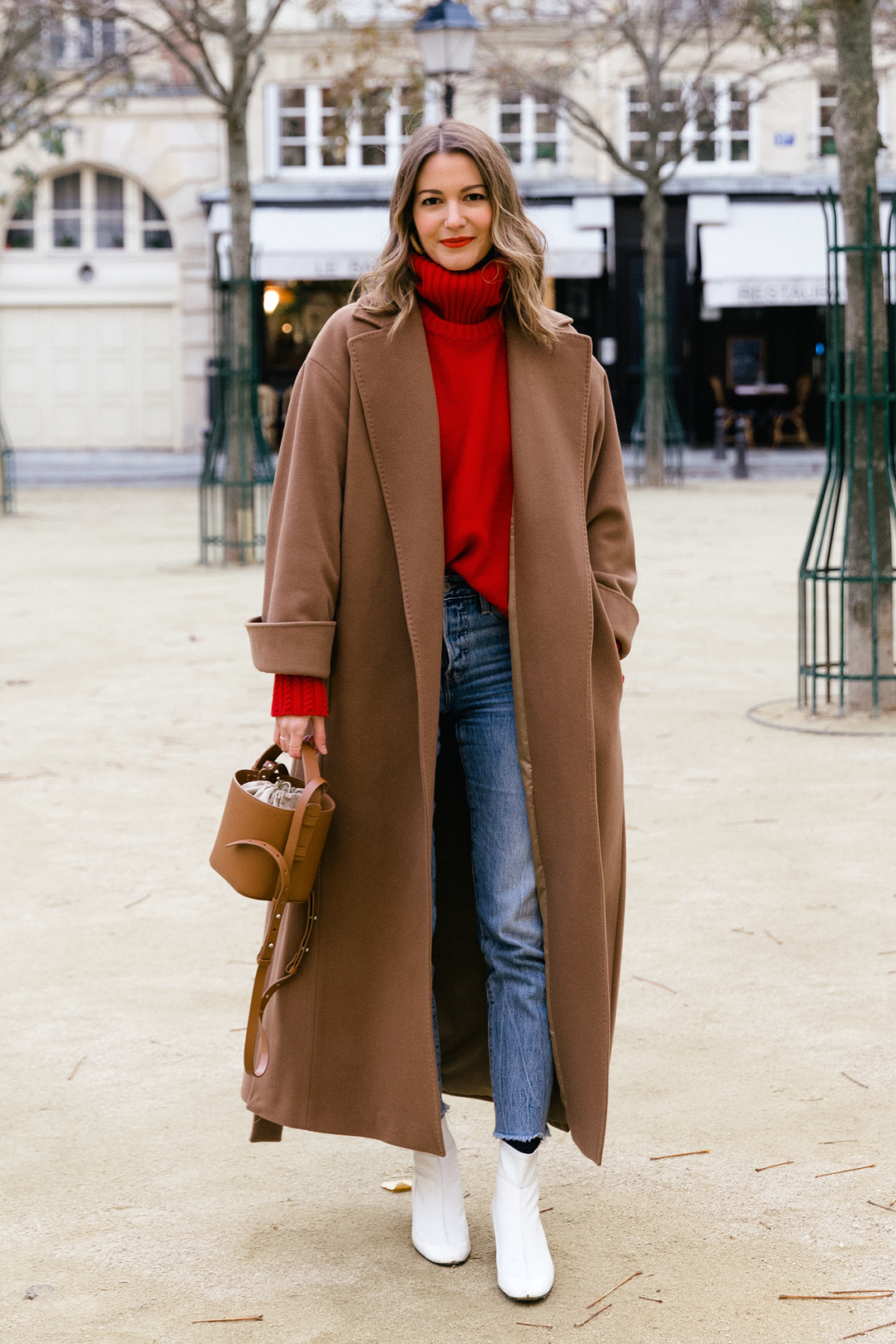 Stylish Holiday Outfit Idea for Christmas and More — Rue Rodier or Marissa Cox in a brown coat, red turtleneck sweater, mini bucket bag, raw-hem jeans, and white boots<
