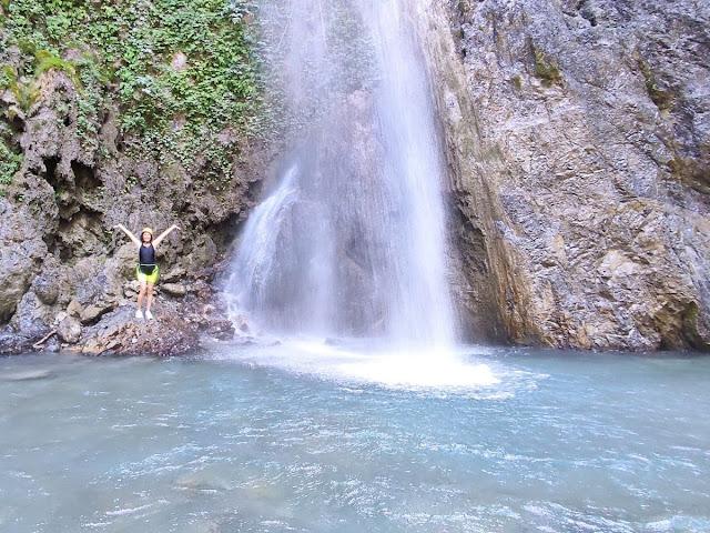 Donna con braccia alzate vicino alla cascata