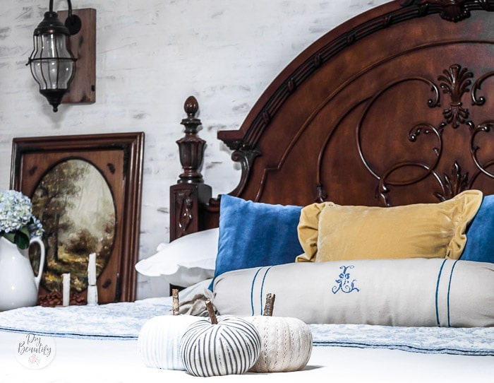 Dark headboard and ornate frame, blue and white quilt, blue and yellow velvet pillows and ticking striped pumpkins