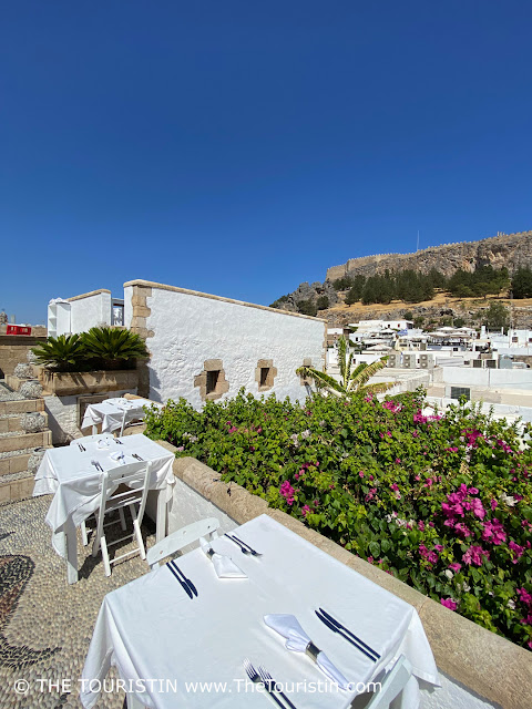 Tables decked in white table cloths in a with pebbles tiled rooftop restaurant in front of a castle on a mountain top.