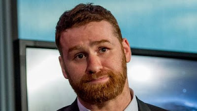 Sami Zayn in professional attire looking perturbed