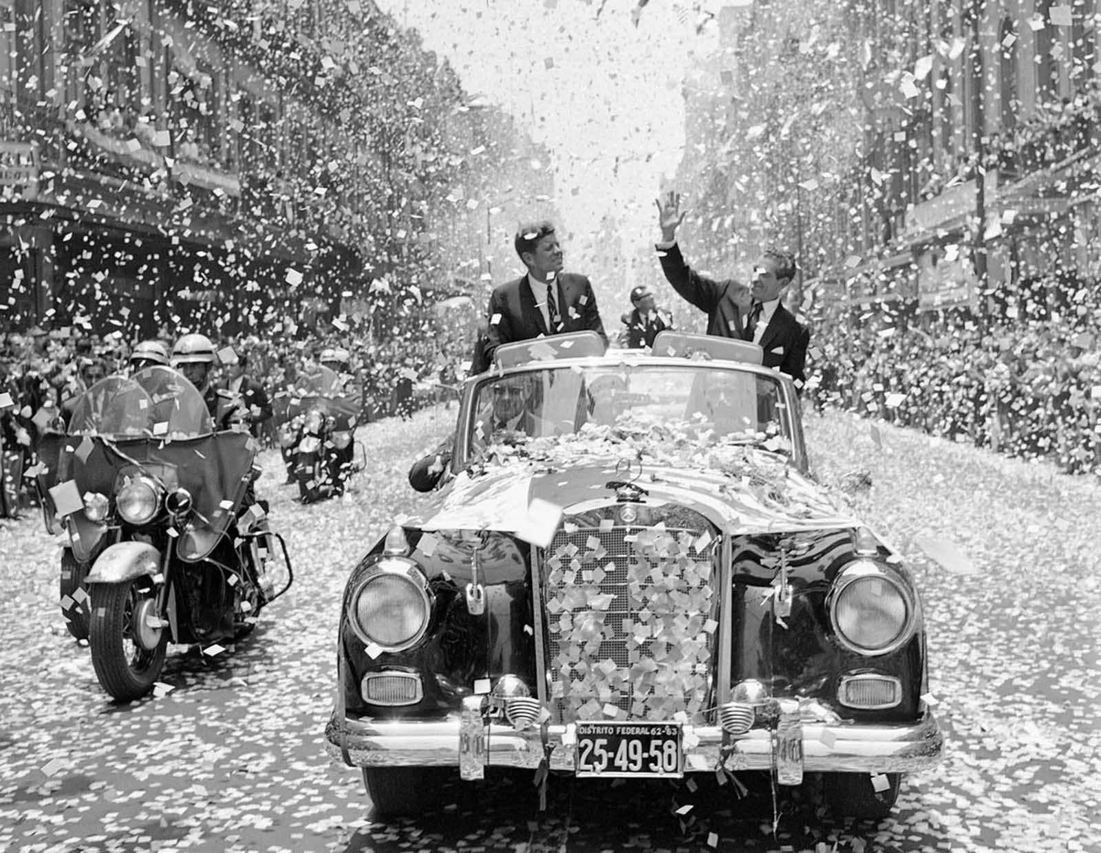 U.S. President John F. Kennedy and Mexican President Adolfo Lopez Mateos are showered with tons of confetti and paper, on June 29, 1962, as they travel down one of Mexico City's boulevards shortly after Kennedy's arrival for a three-day visit.