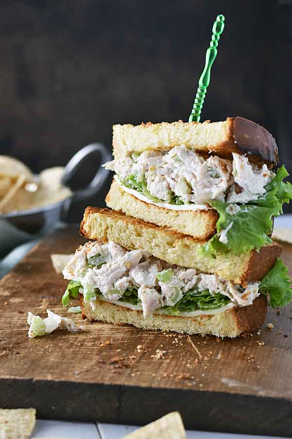 Poached Chicken Salad sandwich stacked on a wooden cutting board and served with chips