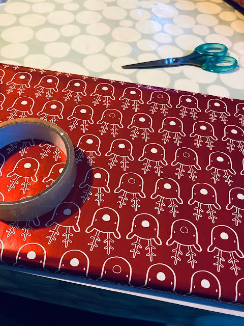 Red shiny reindeer wrapping paper on a present, sellotape and scissors