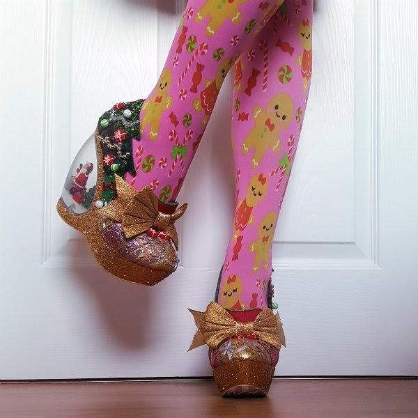lifted leg with pink Christmas tights and snow globe heeled shoes with Christmas tree detail
