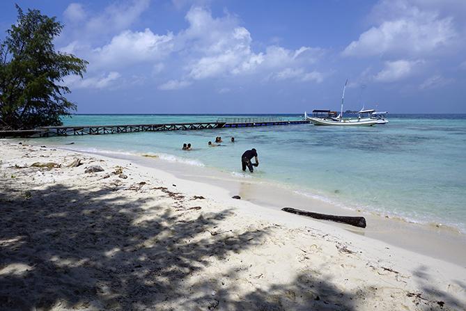 Wisatawan sedang bermain di pasir pantai pulau Sintok