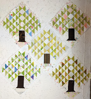 Fine pine tree quilt blocks sewn. Leaves represented by light green triangles with a few other colors like blue, pink, and darker green for depth. for depth