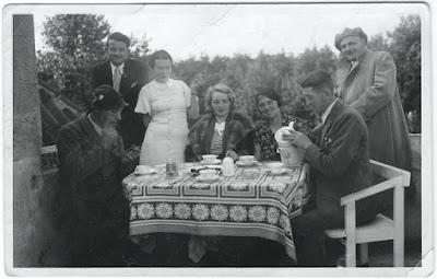Kaffeetafel mit Damen und Herren. Alte Frisuren und Kleider, Bank aus weißgestrichenem Holz, Stofftischdecke. (Kaffeetafel 1927, Originalbild)
