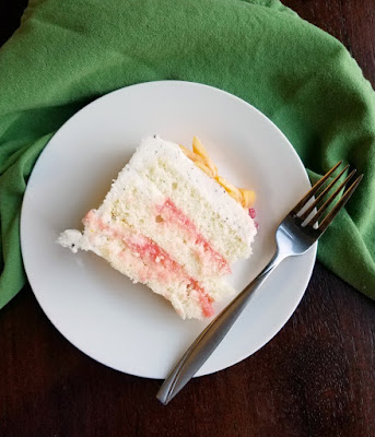 slice of white cake with pink blood orange curd filling between layers
