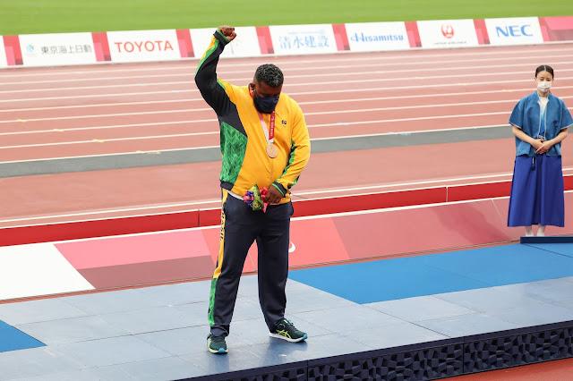 Thiago Paulino, com o uniforme da seleção brasileira composta por casaco verde e calça preta, protesta contra o resultado da prova com o braço direito erguido com os punhos cerrados