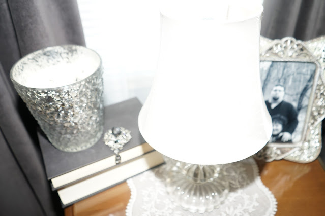 Picture on nightstand, and lamp with lampshade