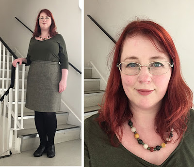 A redheaded white woman in an olive top and skirt, black tights and black shoes.