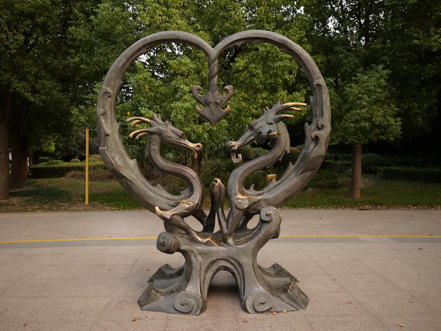 sculpture of two dragons with intertwined tails forming a heart shape