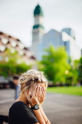 Mujer sentada en un banco tapándose la cara con las manos