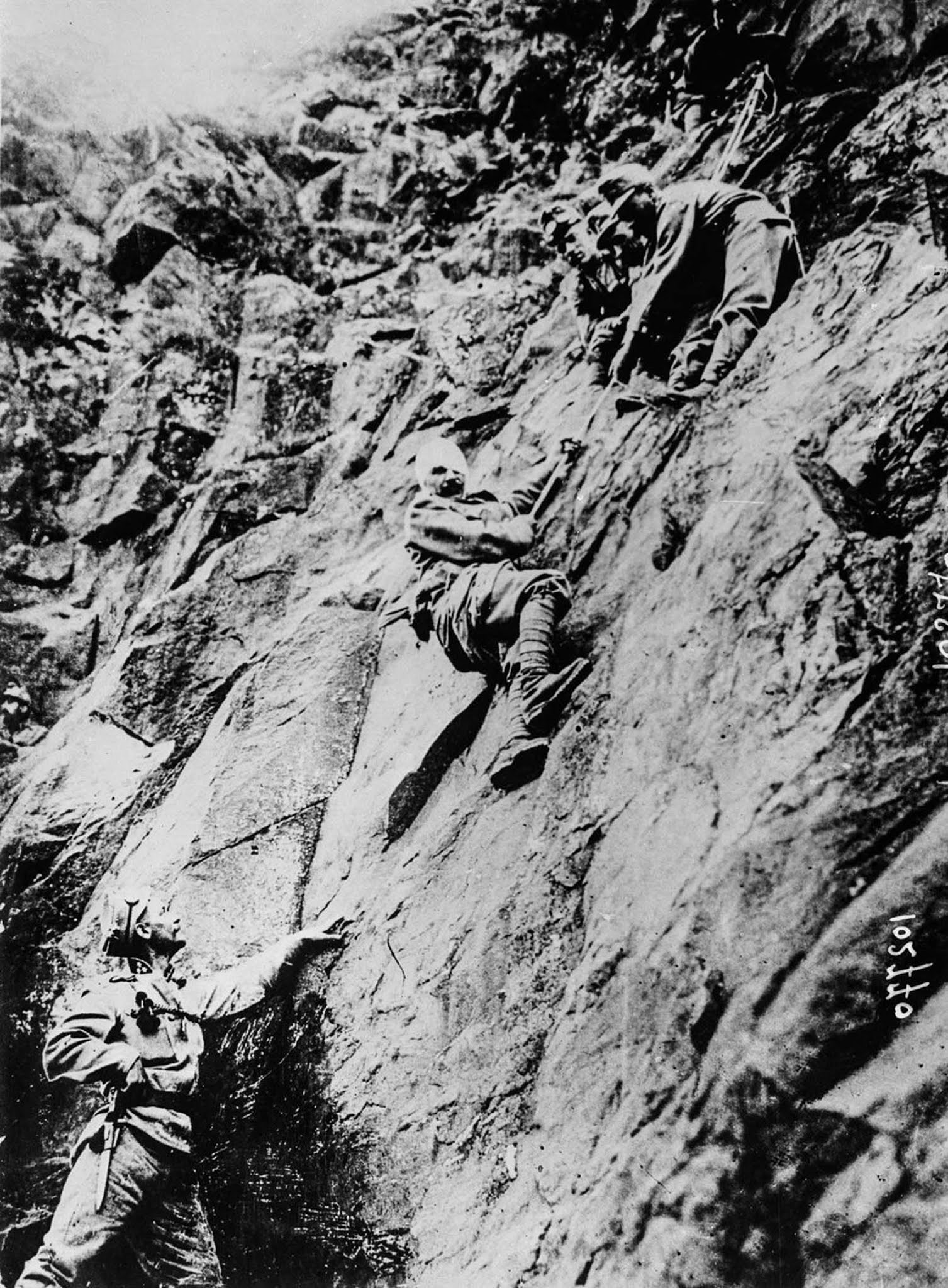 Soldiers lower a wounded comrade down a cliff. 1915.