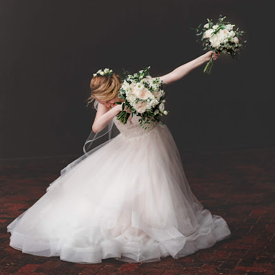 a bride dabbing with two bouquets