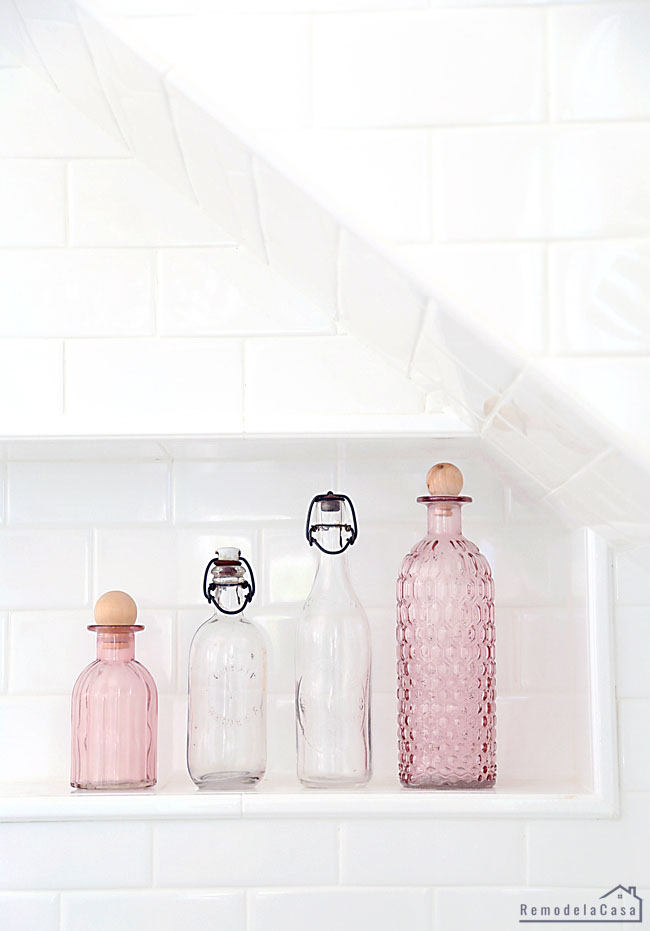 vintage clear and pink glass bottles on shower niche