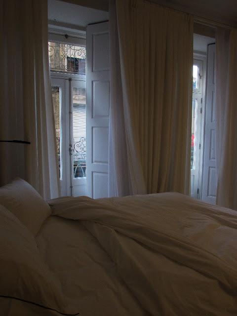 cama de casal desarrumada e portadas para a varanda
