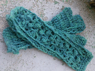 Two crochet fingerless mittens laying on top of each other.  They are worked in fingering-weight yarn.   The mitten on top has a lace and bobbles stitch on the back of the hand, mitten below is palm up, with alternating rows of single crochet and double crochet.  There is a grey cat paw in the top right corner.