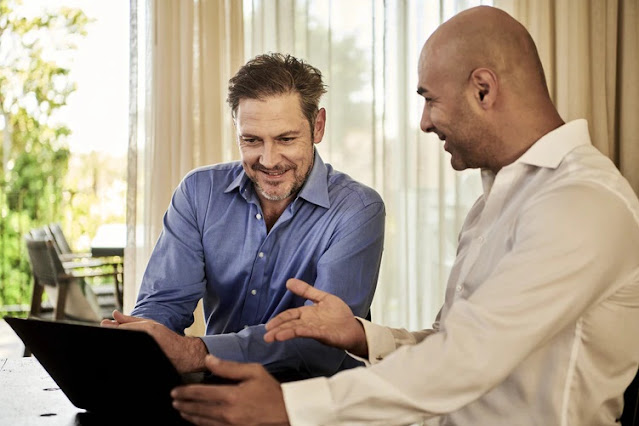 Two men talking and looking at a tablet