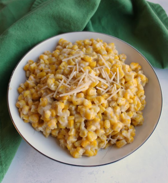 bowl of creamy parmesan corn with shredded cheese on top ready to be served