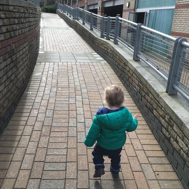 toddler alone running up ramp
