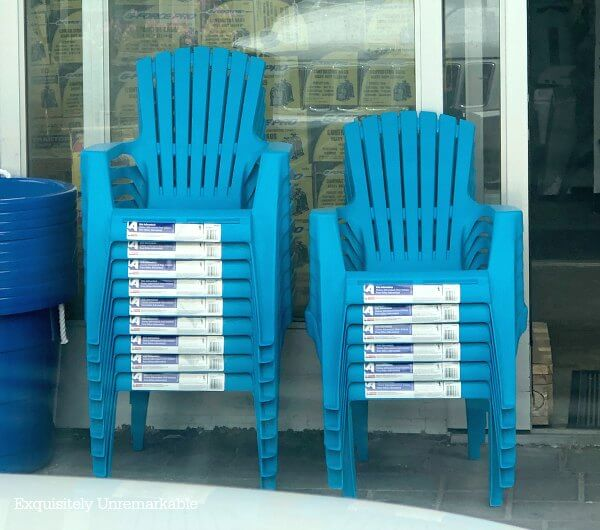 Stacks of blue Plastic Adirondack Chairs in front of a hardware store