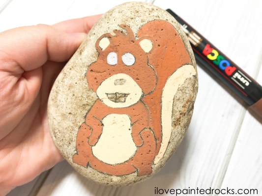 Painting the body of the squirrel on the rock stone with a brown posca pen
