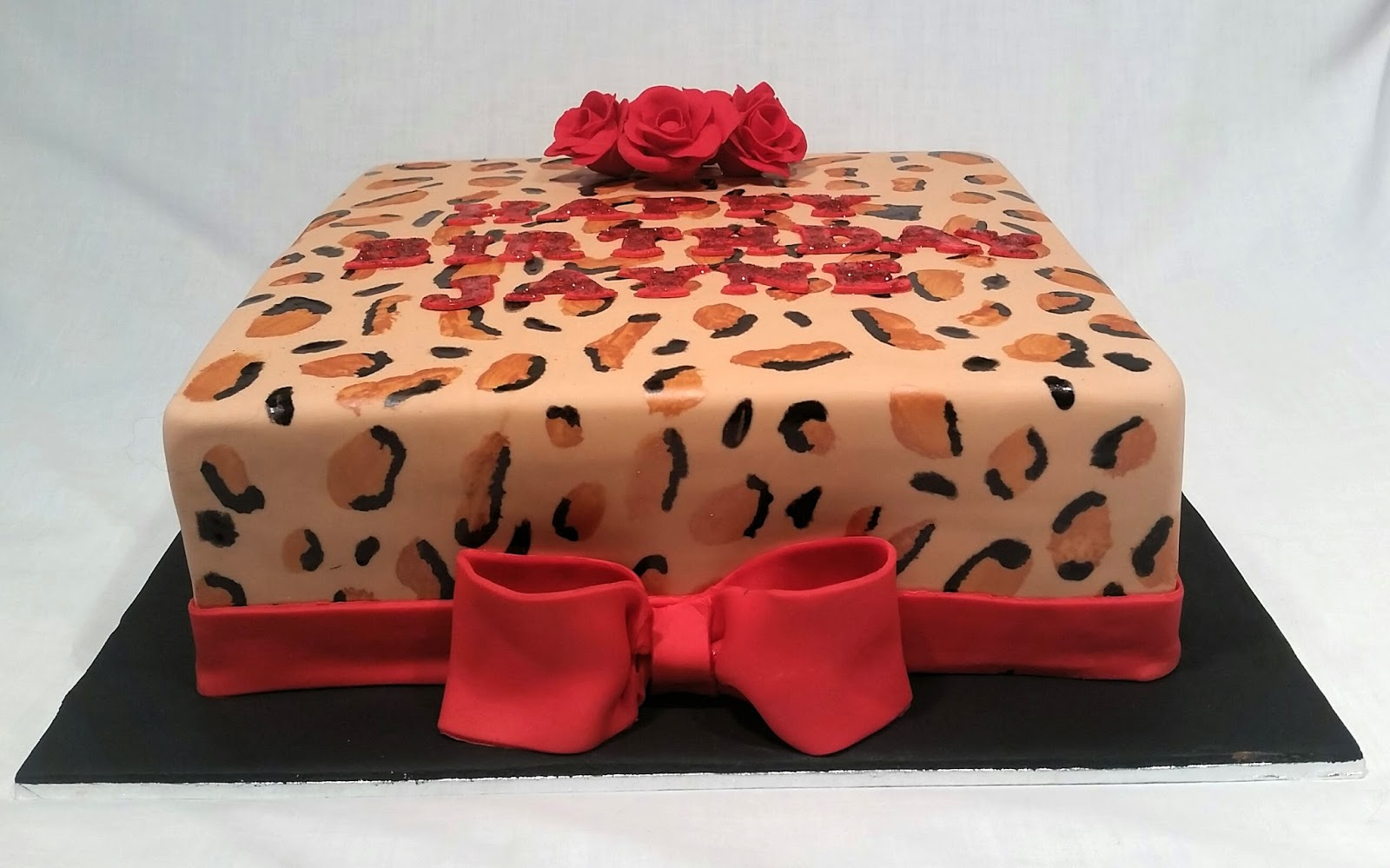 Caramel Mud Cake Filled With Dark Chocolate Ganache Finished Fondant And A Hand Painted Leopard Print Design Made Sugar Roses