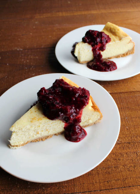 two slices of cheesecake with blackberry sauce