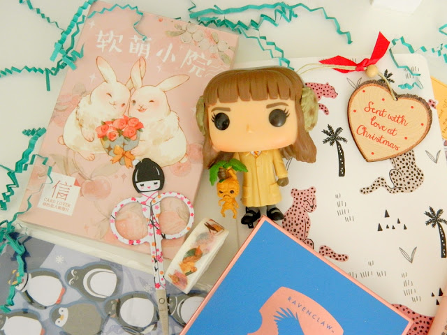 a photo showing a selection of cute item; a box of postcards, a little japanese doll set of nail scissors, a hermione granger pop vinyl figure
