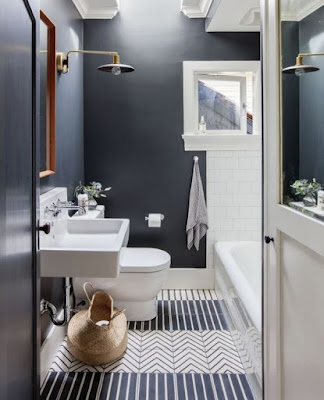 Gray bathroom design features stripe and chevron floor tiles wood framed wall mirror and wall sconce light