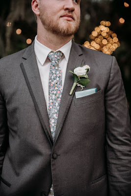 groom with floral print tie
