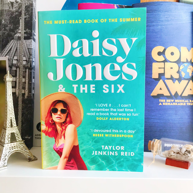 Daisy Jones & The Six by Taylor Jenkins Reid on desk shelf in front of musical programs. Ornament of Eiffel Tower next to it