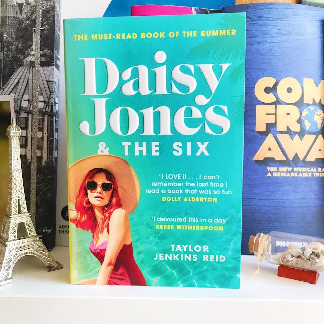 Daisy Jones & The Six by Taylor Jenkins Reid on desk shelf in front of musical programs. Ornament of Eiffel Tower next to it