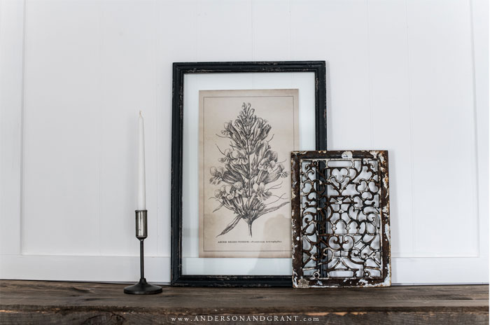 Candlestick, botanical print, and metal art on mantel