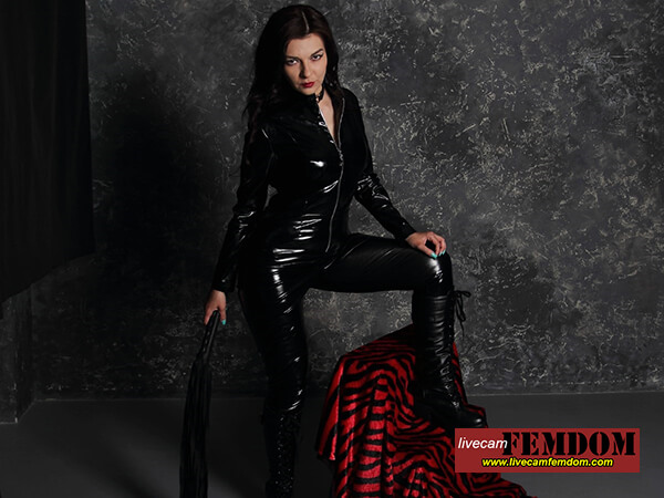 Black PVC catsuit Domina with flogger wears long black leather boots