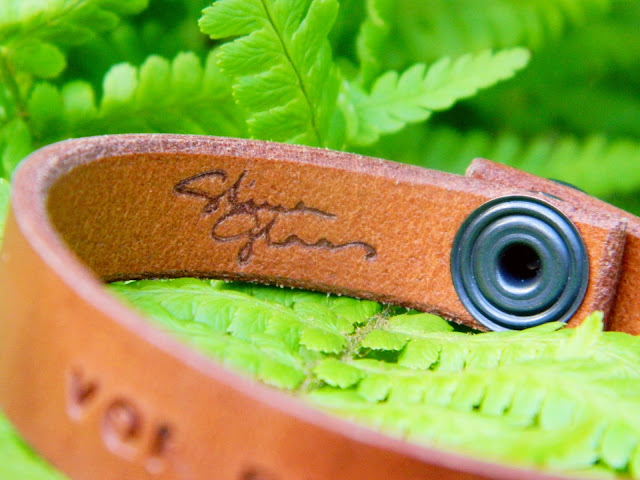 A brown leather bracelet made by Stina Glaas sitting on a green fern