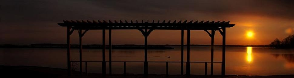 A yellow sunrise reflecting off Lake Couchiching with the Pergola at Veteran'ts Park in the foreground.