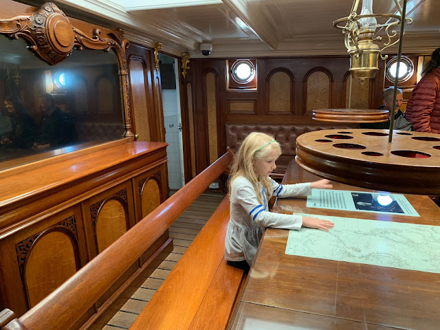 A young girl sitting at the Captain's Table in the Cutty Sark