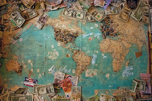 A map of the world with pins in it and dollar banknotes around it